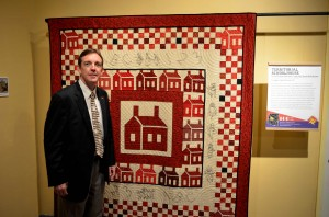 "Ken Bennett with Prescott's Heritage Quilt And Study Group of the Sharlot Hall Museum's quilt, ""Territorial Schoolhouse."""