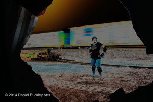 Rowena Davis of Tucson Roller Derby, seen through wrecked railroad car.