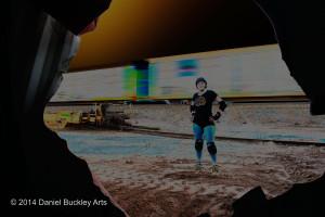 Rowena Davis of Tucson Roller Derby, seen through wrecked railroad car.