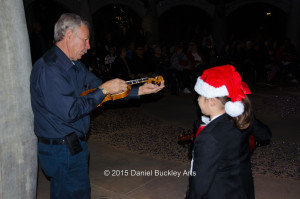 Alfredo Valenzuela, aka Dr. V, tunes violins at a Christmas performance by Mariachi Las Aguilitas de Davis Elementary at the University of Arizona.